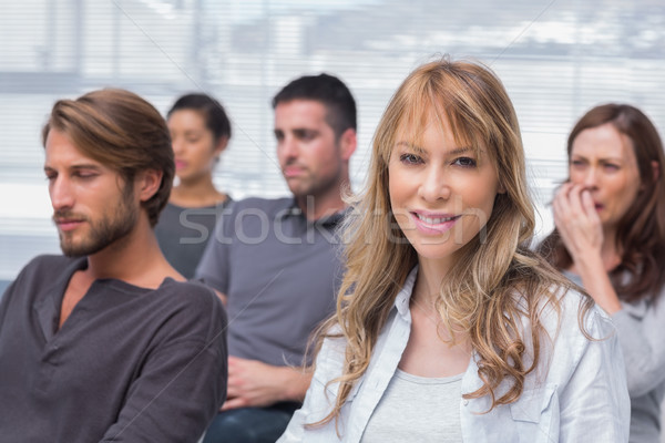 Patients listening in group therapy with one woman smiling Stock photo © wavebreak_media