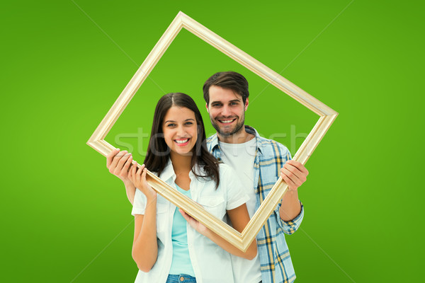 Composite image of happy young couple holding picture frame Stock photo © wavebreak_media