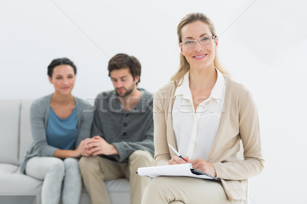 Female counselor with young couple in background Stock photo © wavebreak_media