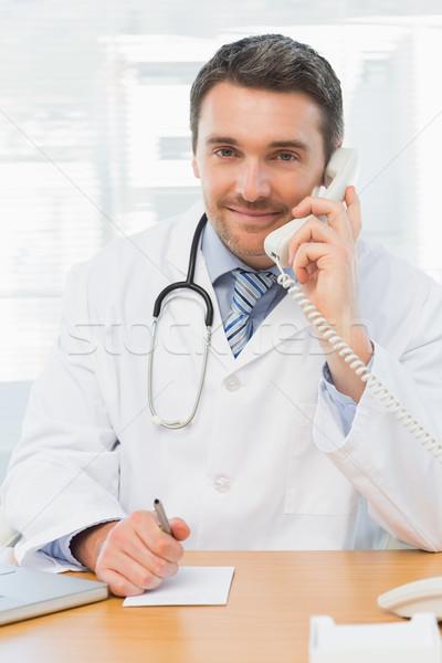 Photo stock: Souriant · médecin · de · sexe · masculin · téléphone · écrit · note · portrait