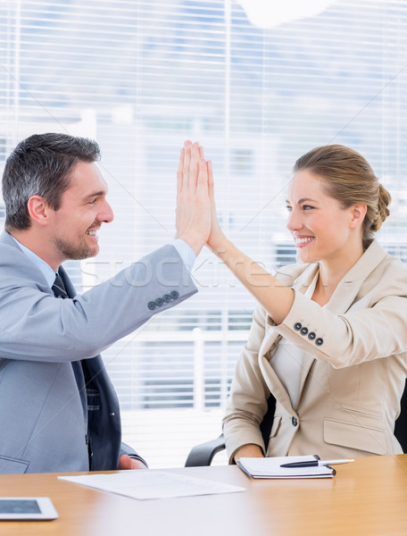 Smartly dressed colleagues giving high five in business meeting Stock photo © wavebreak_media