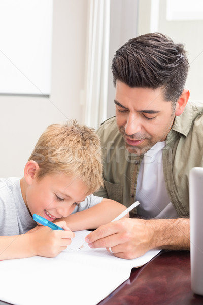 Father and son sitting at table colouring together Stock photo © wavebreak_media