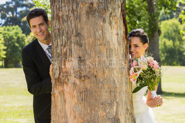 Happy newlywed couple behind tree trunk in park Stock photo © wavebreak_media