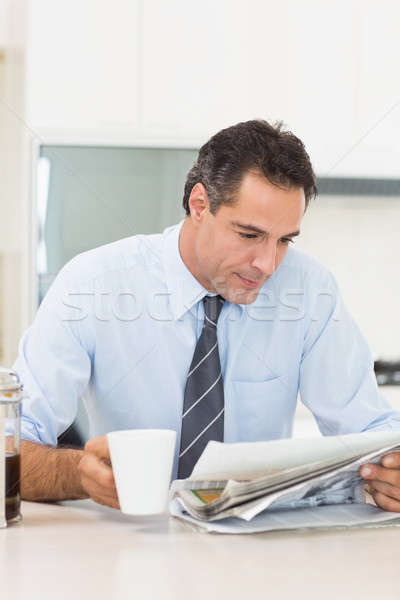 Well dressed man with coffee cup reading newspaper in kitchen Stock photo © wavebreak_media