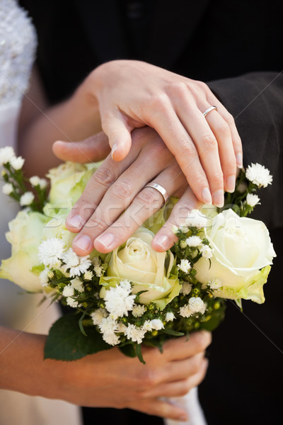 Newlywed couple with wedding rings and bouquet Stock photo © wavebreak_media