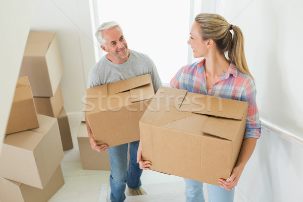 Happy couple carrying cardboard moving boxes  Stock photo © wavebreak_media