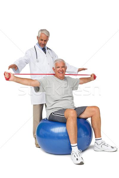Mhysiotherapist looking at senior man sit on exercise ball with  Stock photo © wavebreak_media