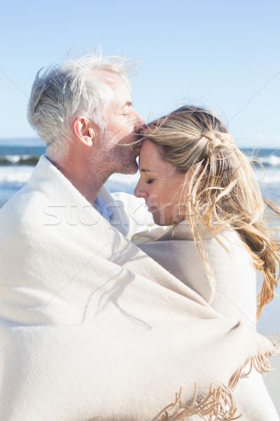 Affectionate couple wrapped up in blanket on the beach Stock photo © wavebreak_media