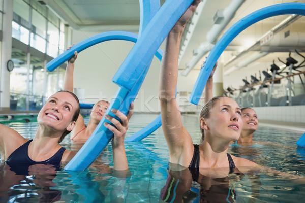Happy fitness class doing aqua aerobics with foam rollers Stock photo © wavebreak_media