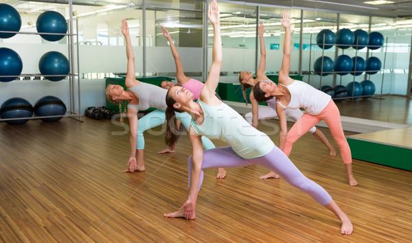 Yoga class in extended triangle pose in fitness studio Stock photo © wavebreak_media