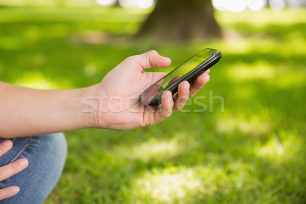 Woman sending a text on smartphone in the park Stock photo © wavebreak_media