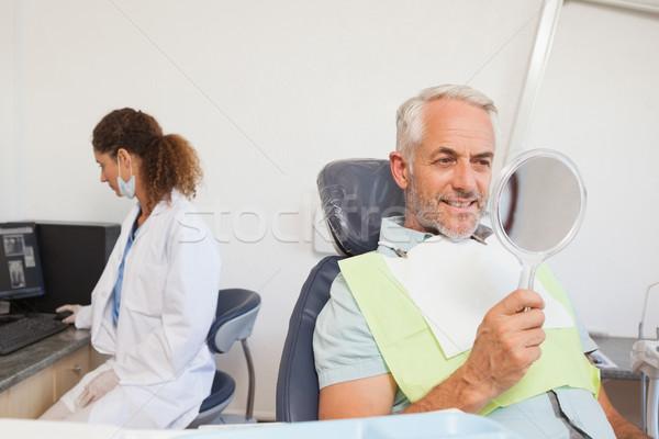 Patient admiring his new smile in the mirror Stock photo © wavebreak_media