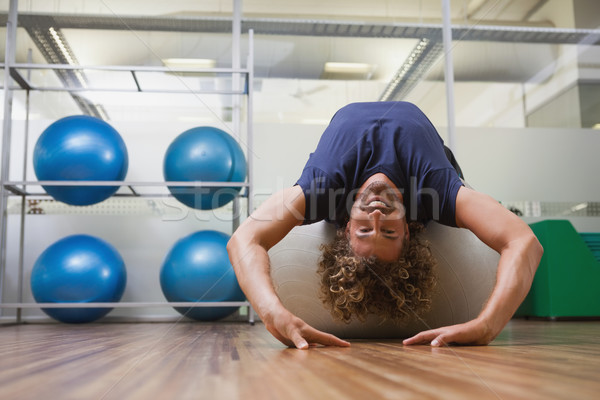 Handsome man stretching on fitness ball in gym Stock photo © wavebreak_media