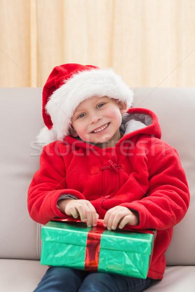 Festive little boy smiling at camera with gift Stock photo © wavebreak_media
