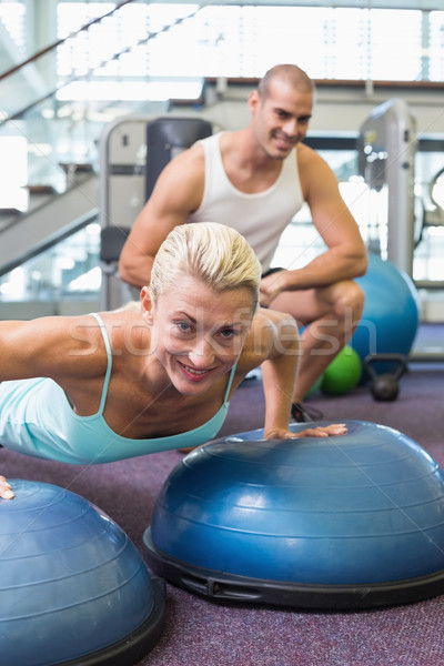 Trainer assisting woman with push ups at gym Stock photo © wavebreak_media