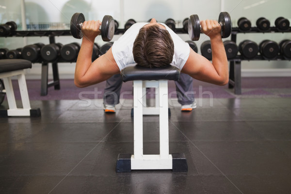 Fit man lifting dumbbells lying on the bench Stock photo © wavebreak_media