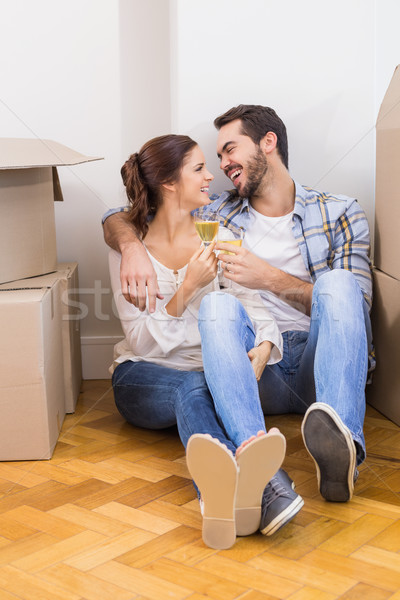 Cute couple toasting with champagne on floor Stock photo © wavebreak_media