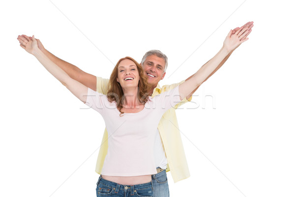 Casual couple smiling with arms raised Stock photo © wavebreak_media