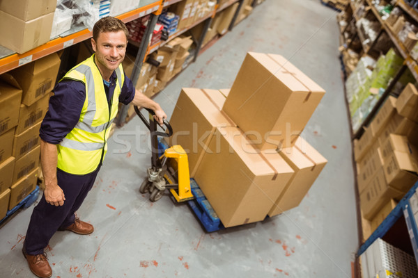 Worker with trolley of boxes smiling at camera Stock photo © wavebreak_media