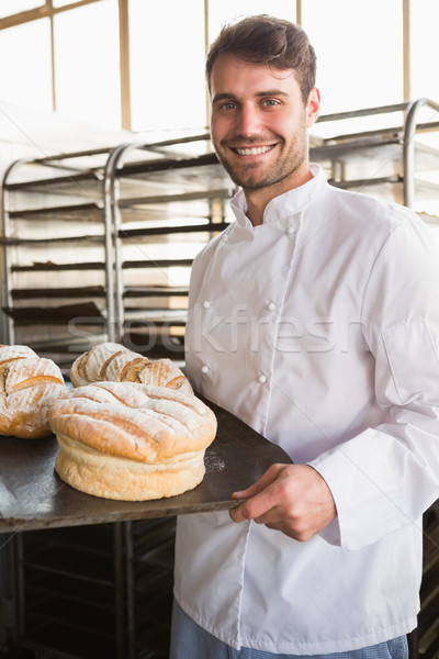 Stock photo: Happy baker showing tray with bread