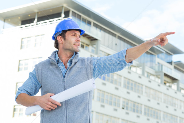 Architect with blueprint pointing away Stock photo © wavebreak_media