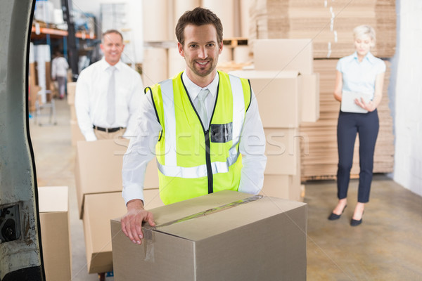 Stock photo: Delivery driver loading his van with boxes