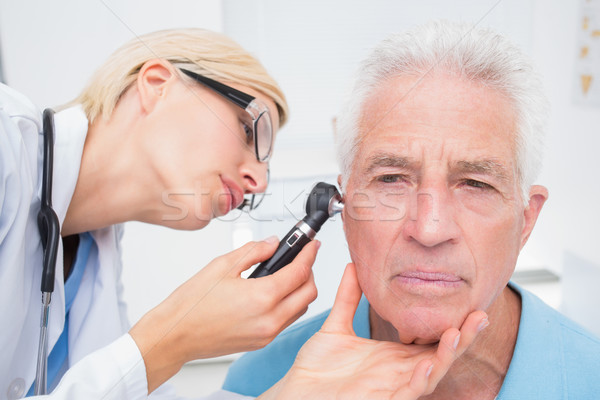 Doctor examining senior patients ear with otoscope Stock photo © wavebreak_media