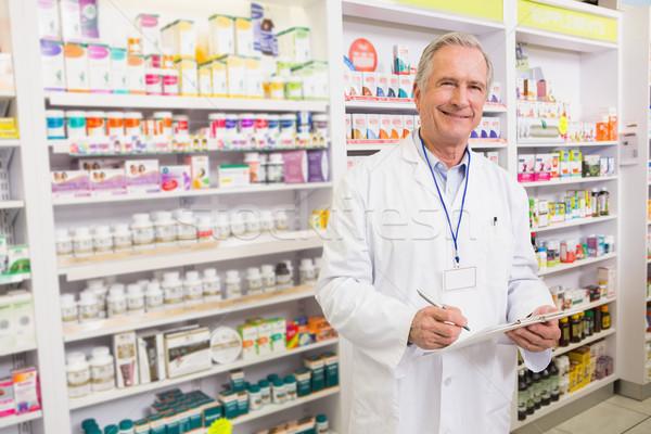 Smiling senior pharmacist writing on clipboard Stock photo © wavebreak_media