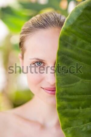 Pretty woman looking through leaves  Stock photo © wavebreak_media