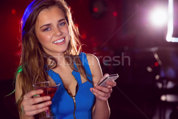 Pretty girl drinking a cocktail and texting Stock photo © wavebreak_media