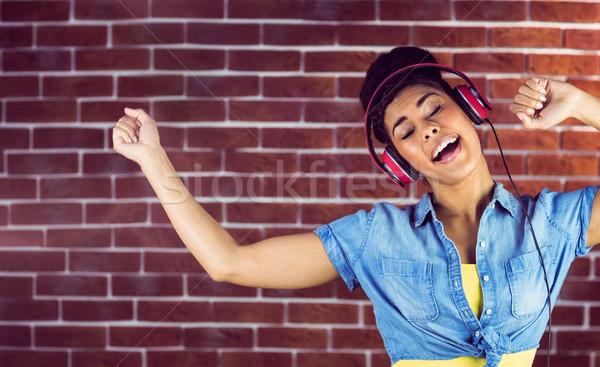 Uśmiechnięta kobieta taniec słuchawki murem moda czerwony Zdjęcia stock © wavebreak_media