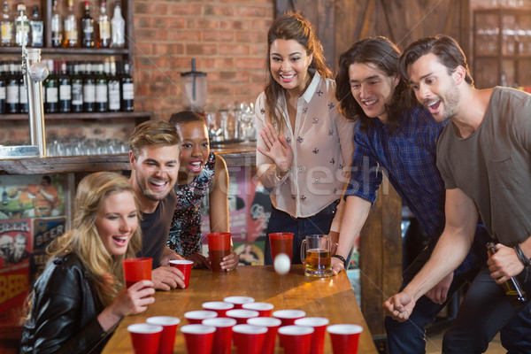Friends cheering while woman playing beer pong in bar Stock photo © wavebreak_media