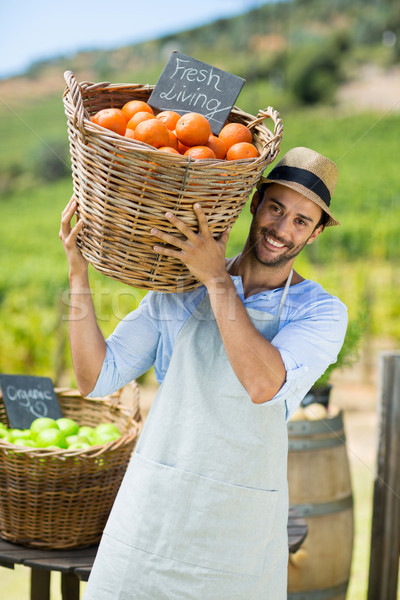 Portrait of happy farmer carrying by fresh oranges in container Stock photo © wavebreak_media