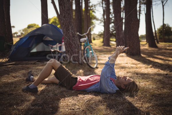 Side view of man using smart phone while lying on field Stock photo © wavebreak_media