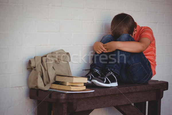 Full length of unhappy boy sitting on bench by wall Stock photo © wavebreak_media