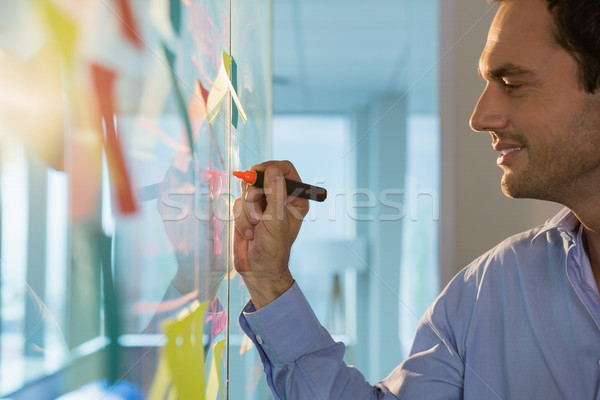Male executive writing on glass board with a marker Stock photo © wavebreak_media