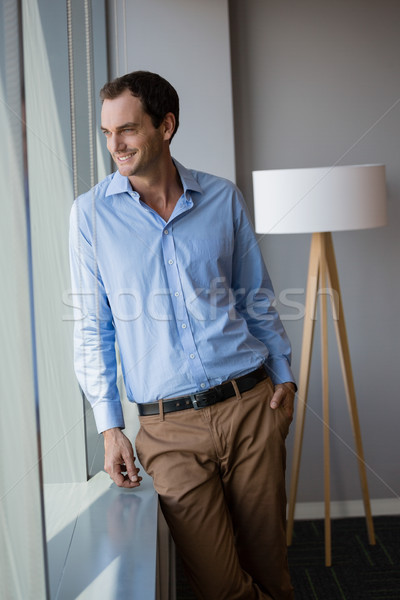 Male executive looking through window in office Stock photo © wavebreak_media