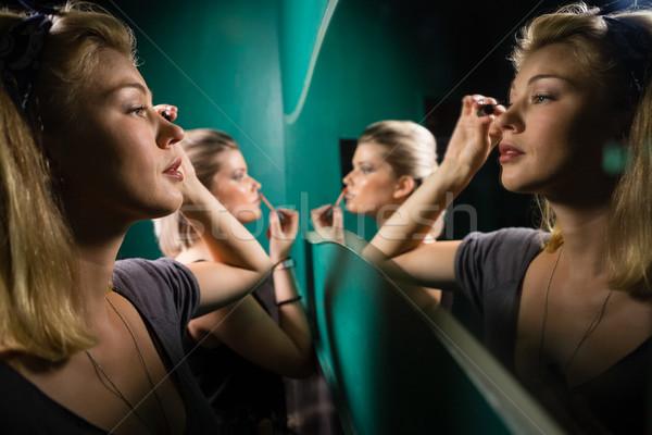 Woman applying eyeliner while looking at mirror Stock photo © wavebreak_media
