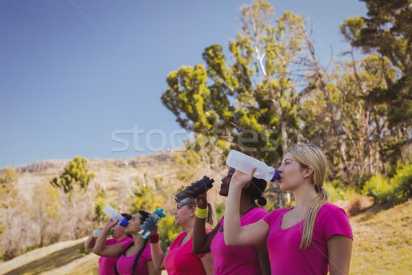 Grupo mujeres agua potable arranque campamento Foto stock © wavebreak_media
