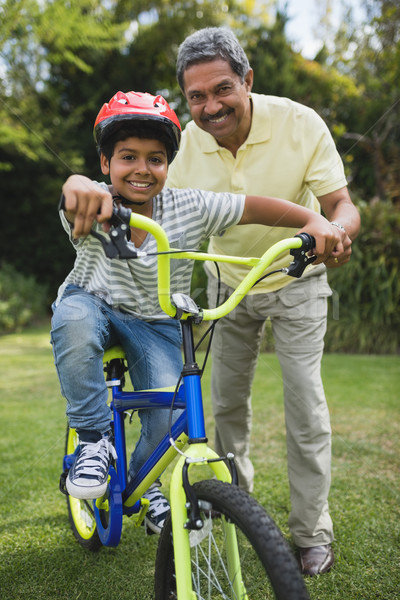 Portrait of grandfather assisting grandson while riding bicycle Stock photo © wavebreak_media