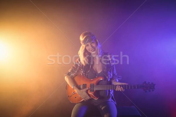 Confident female guitarist performing in music concert Stock photo © wavebreak_media