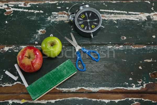 Apple, alarm clock, duster, scissors and chalk on wooden table Stock photo © wavebreak_media