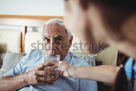 Side view of female doctor giving water to senior patient Stock photo © wavebreak_media