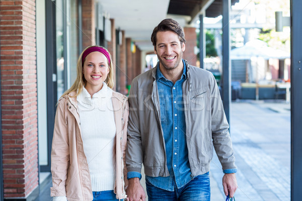 Smiling couple with shopping bags holding hands Stock photo © wavebreak_media