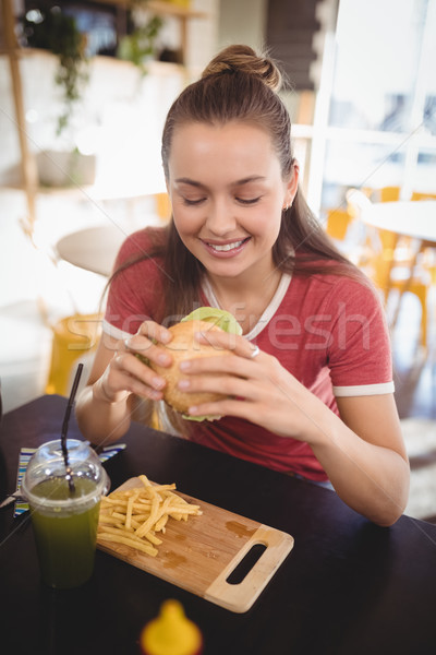 Smiling young gorgeous woman eating burger at coffee shop Stock photo © wavebreak_media