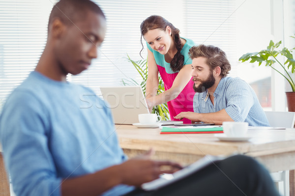 Woman pointing at laptop while discussing with man at desk  Stock photo © wavebreak_media