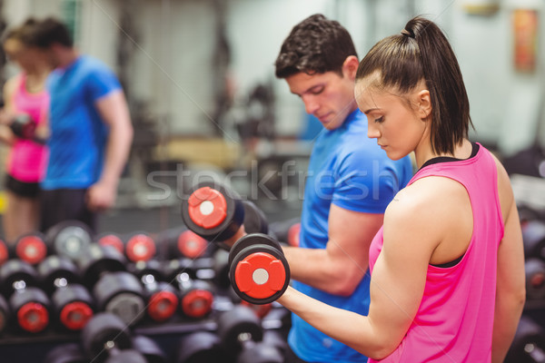 Woman lifting dumbbells with her trainer Stock photo © wavebreak_media