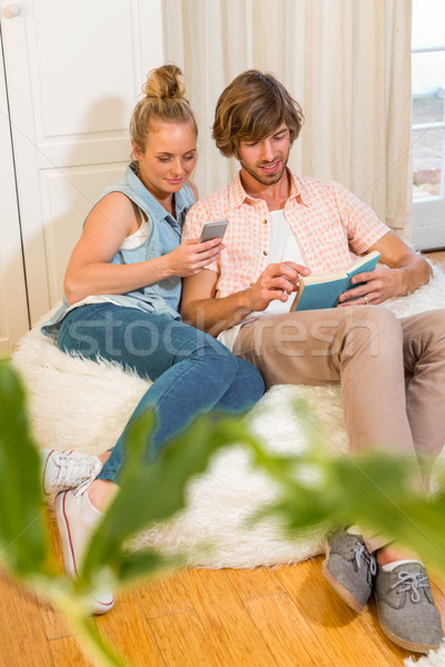 Cute couple reading a book and using smartphone Stock photo © wavebreak_media