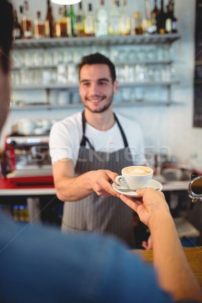 Customer taking coffee from happy waiter at cafe Stock photo © wavebreak_media