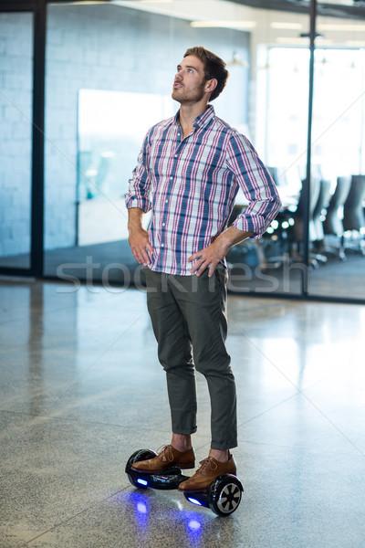 Graphic designer standing on hoverboard in office Stock photo © wavebreak_media